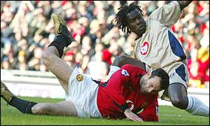 Linvoy Primus of Portsmouth fouls Ryan Giggs to give away a penalty