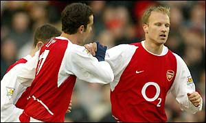Dennis Bergkamp is congratulated after scoring his 100th goal for Arsenal