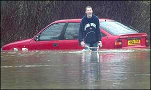 Boy cycles in flooded street in front of submerged car