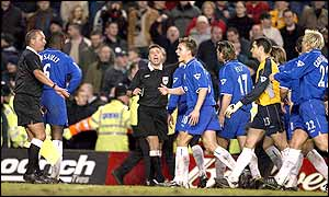 Referee Mark Halsey and his assistant are surrounded by Chelsea players as he beckons Cudicini forward