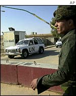 Iraqi soldier watches UN inspectors