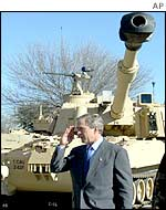 US President George W Bush salutes in front of a tank