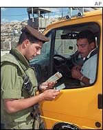 Israeli soldier stops Palestinian at checkpoint