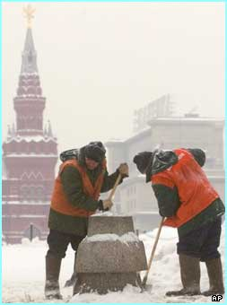 Workers in Moscow's Red Square work to clear a monument after a heavy snowfall