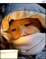 A child holds a candle during an anti-US rally near the US Embassy in Seoul 4 January 2003