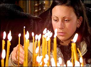 A woman lights candles for Christmas in the Bosnian capital, Sarajevo