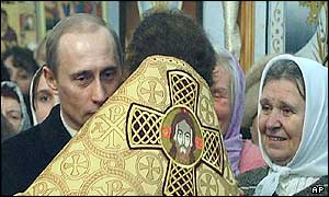 Russian President Vladimir Putin is embraced by an Orthodox priest at a Christmas service