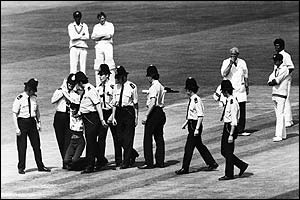 Policemen lead a demonstrator off the pitch during the match between Australia and Sri Lanka