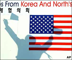A banner is shadowed by a South Korean citizen group leader waving the flags of the US and South Korea