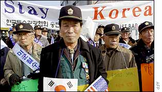 South Koreans carry pro-US placards along with US and South Korean flags during a rally outside the US air force base in Osan, south of Seoul, 8 January 2003