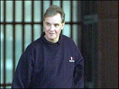 Jonathan Aitken with prison gates behind him