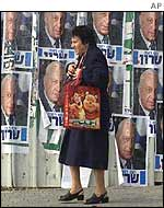 A woman walks in front of election campaign posters