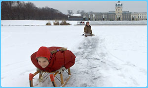 Children play on the frozen lake in front of Berlin's Charlottenburg Castle