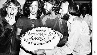 Andy Gibb eats a cherry from his birthday cake held by Maurice, in Florida 1979