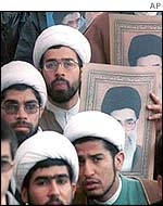 Protesters hold pictures of Ayatollah Ali Khamenei