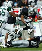 Raiders running back Charlie Garner leaps over team-mate Tim Brown