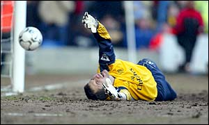 Chelsea goalkeeper Carlo Cudicini dives to try to stop Charlton scoring