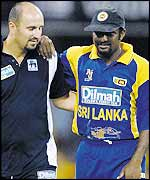 Muttiah Muralitharan is helped from the field by the Sri Lankan physio