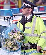 A policeman delivers a tribute for Mr Oake
