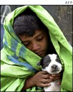 A Bangladeshi homeless boy wraps his pet dog with the blanket to keep it warm in Dhaka