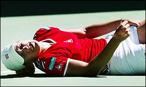 Justine Henin-Hardenne falls to the floor in pain