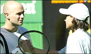 Andre Agassi shakes hands at the net with Guillermo Coria