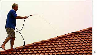 Home-owner sprays his roof with water