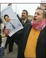 Supporter demonstrates with picture of Saddam Hussein