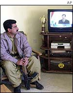 Kurdish fighter watches Saddam Hussein speech on TV