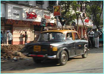 Another taxi waiting in the high street in Bombay. It's a tight squeeze to fit inside!