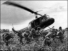 Helicopter taking off, leaving troops on ground