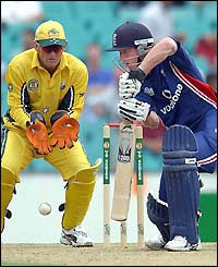 Australian wicket-keeper Adam Gilchrist concentrates as England's Paul Collingwood hits out