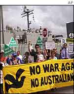 Protestors gather outside the Garden Island Naval Base in Sydney as HMAS Kanimbla, back, prepares to sail