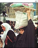 A woman collects her food rations in Baghdad
