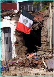 The Mexican flag flies over the rubble after Tuesday's earthquake