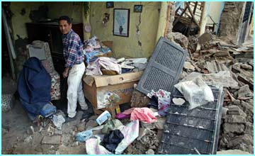A man tries to collect his belongings from the ruin of his house, in the mountainous region of Colima