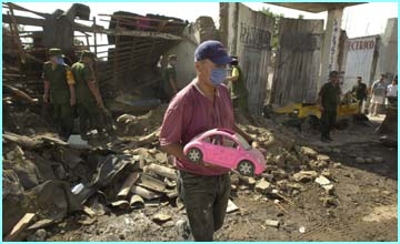 A man retrieves his stuff from the wreckage