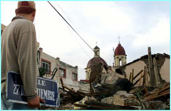 This man holds a street sign which has fallen down, while he looks at the rest of the damage