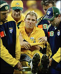 Warne is stretchered off after injuring his shoulder
