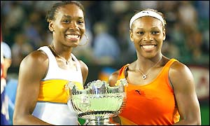 Venus and Serena Williams pose with their winners trophy