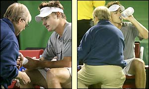 Andy Roddick is treated by the trainer during a three minute injury time-out at the end of the second set