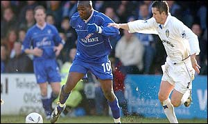 Gillingham's Guy Ipoua is held back by Leeds United's Gary Kelly