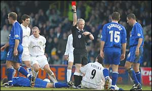 Referee Neale Barry shows Mark Viduka of Leeds the red card