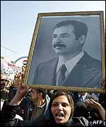 Iraqi woman with portrait of Saddam