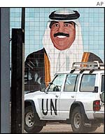 A UN weapons inspectors vehicle enters Ibn al-Haitham manufacturing facility for missile components past a mural of Iraqi leader Saddam Hussein in Baghdad