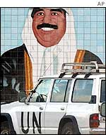 UN vehicle in front of a mural of Saddam Hussein