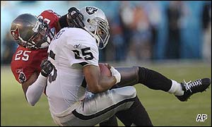 Tampa Bay Buccaneers cornerback Brian Kelly, left, tackles Oakland Raiders running back Charlie Garner