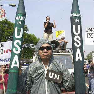 Demonstrator in Manila dressed up UN arms inspectors holding mock missile