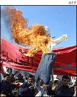 Iraqi protesters burn an effigy of President Bush in Baghdad
