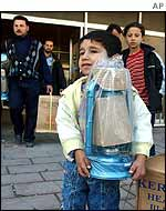 Iraqi child holds lantern as his family shops for emergency provisions
